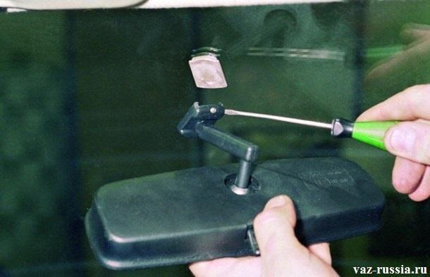 Отворачивание стопорного винта кронштейна зеркала