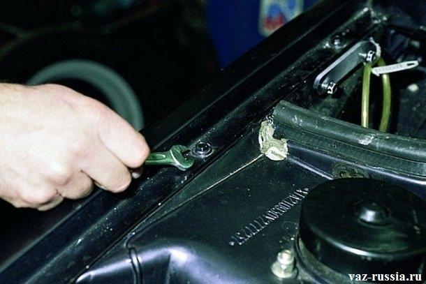 Отворачивание верхнего болта крепления крыла к кузову