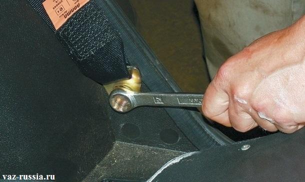 Отворачивание ключом болта крепления нижней части ремня