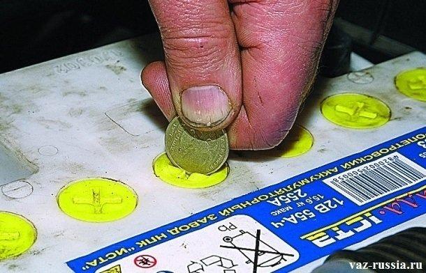 Удерживая в руке монету выворачивание ей пробки отсека аккумулятора