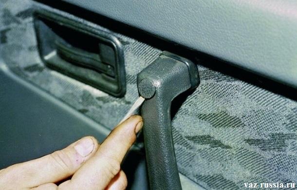Извлечение заглушек, которые закрывают винты крепления ручки двери