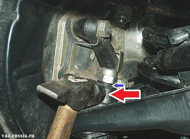 Молотком постучите по нижнему ушку поворотного кулака, который указан красной стрелкой и после резких постукиваний палец шарнира должен будет выйти, и тем самым повиснуть на гайке