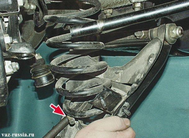 Поддевание монтажной лопаткой нижней части пружины, и снятие ее с автомобиля