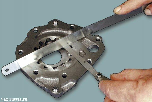 Измерение осевого зазора ведомой шестерни маслонасоса с помощь металлической линейки и щупа определённого размера