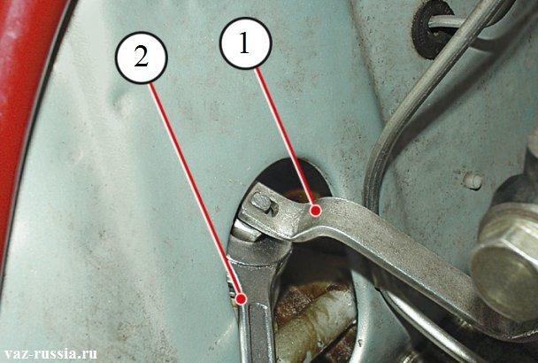 Удерживание специальным ключом под цифрой «1» штока от проворачивания. А гачным ключом в это время под цифрой «2» отворачивание гайки.