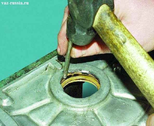 Извлечение сальника из отверстия в крышке, при помощи молотка и бородка