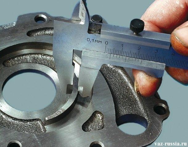 Проверка при помощи штангенциркуля толщины сегмента корпуса маслонасоса