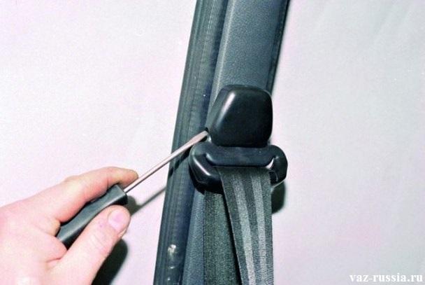 Отсоединение при помощи отвертки, верхней накладки кронштейна ремня