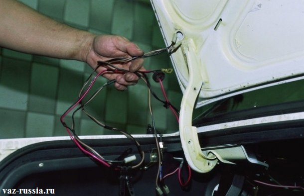 Извлечение жгута проводов из отверстия в багажнике