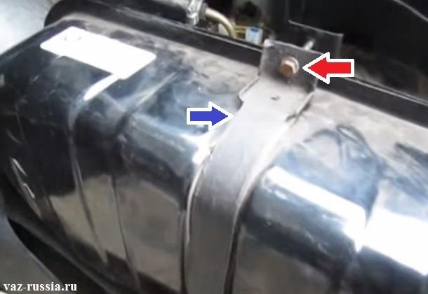 Красной стрелкой указан болт который нужно отвернуть, а синей указан хомут который нужно положить в нижнюю часть багажного отделения после отворачивания удерживающего болта