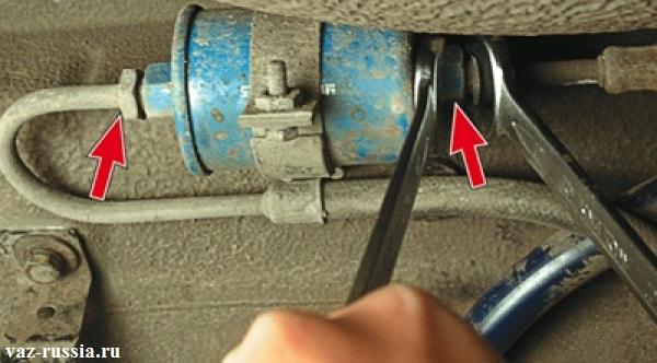 Ослабьте две гайки при помощи двух гаечных ключей, которые крепят топливные трубки к данному фильтру