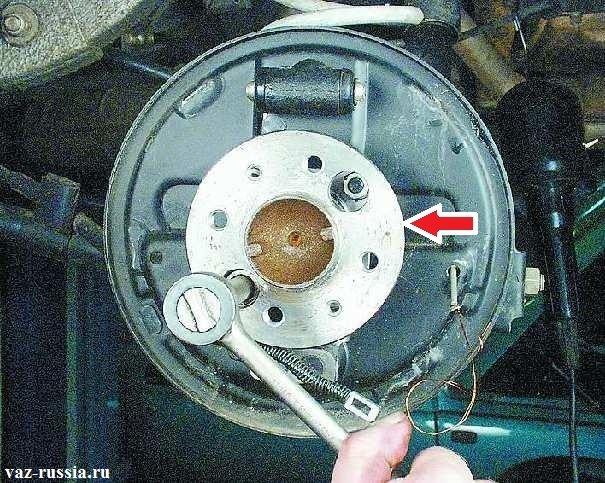 Закручивание гаек крепящих тормозной щиток, добраться до них можно посредством вращения фланца ступицы