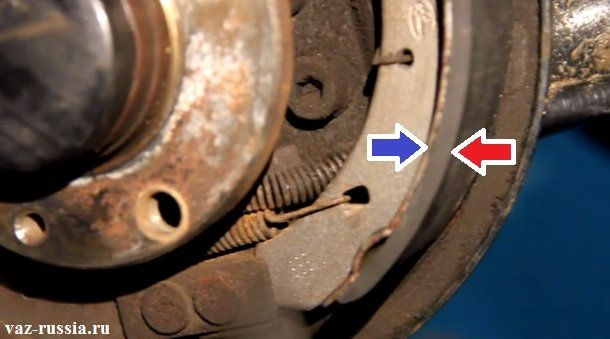 Красная стрелка указывает на тормозную накладку, а синей указана сам корпус тормозной колодки
