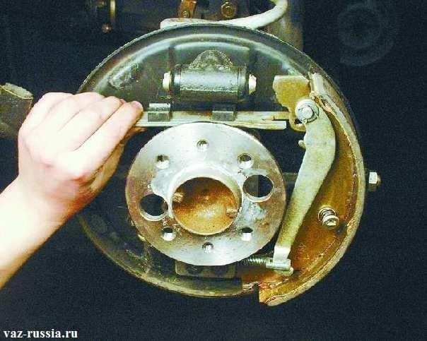 Выведение из зацепления с задней колодой распорной втулки и после чего снятие данной втулки
