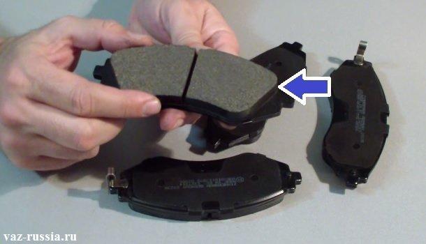 В руке человек держит новую тормозную колодку, а синей стрелкой указана накладка данной колодки, после стирания которой данную колодку нужно будет поменять на новую
