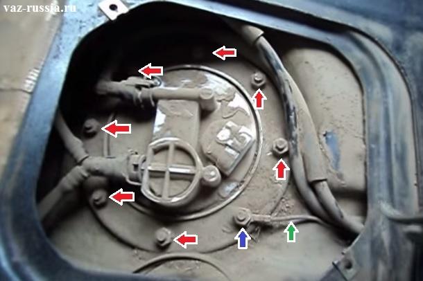 Стрелками указаны восемь гаек которые крепят сам насос к бензобаку автомобиля, но под одной из этих гаек находится ещё и клемма которая указана зелёной стрелкой, поэтому аккуратно снимите и отведите её в сторонку чтобы не мешала замене