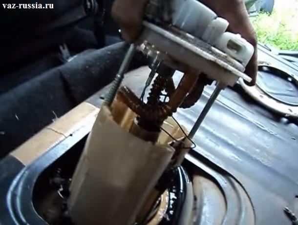 Извлечение насоса из отверстия которое находится в бензобаке автомобиля