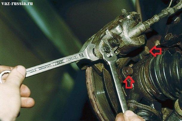 Стрелками указаны болты крепящие тормозной суппорт к поворотному кулаку, после их отворачивания суппорт можно будет снять с автомобиля
