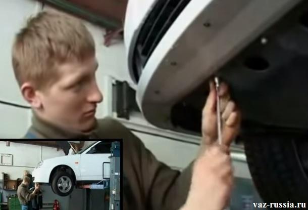 Выворачивание гаек крепления брызговика двигателя, к передней части бампера автомобиля