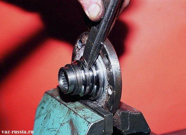Сбивание кольцо подшипника с самой длинной части ступицы при помощи зубила