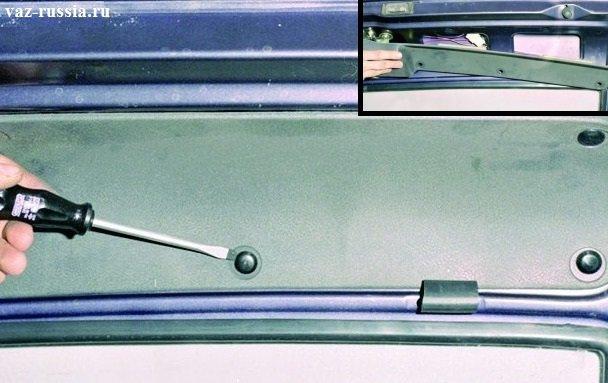 Поддевание с помощью отвёртки пистонов, которые удерживают обшивку двери багажника и вследствие чего снятие её