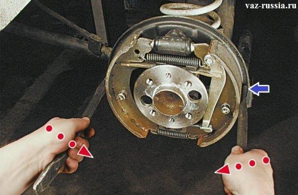 Сведение обоих тормозных колодок друг к другу, при помощи двух монтажных лопаток