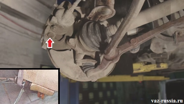 Выворачивание нижнего болта направляющего пальца крепления нижней части скобы тормозного суппорта
