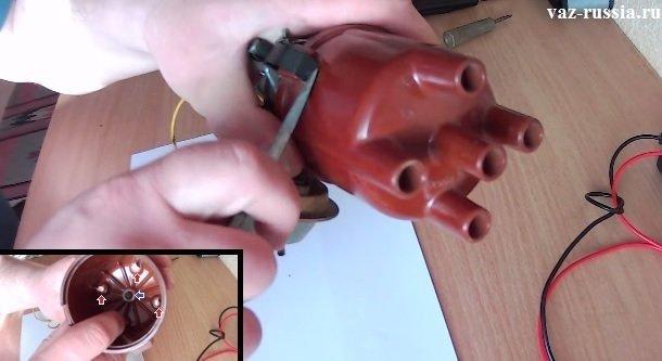 Поддевание при помощи отвёртки боковых держателей которые крепят крышку к распределителю и её снятие