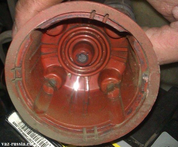 Крышка распределителя снятая с другого автомобиля, для наглядности на ней можно видеть окисленные контакты и сломанный центральный стержень, что в свою очередь недопустимо