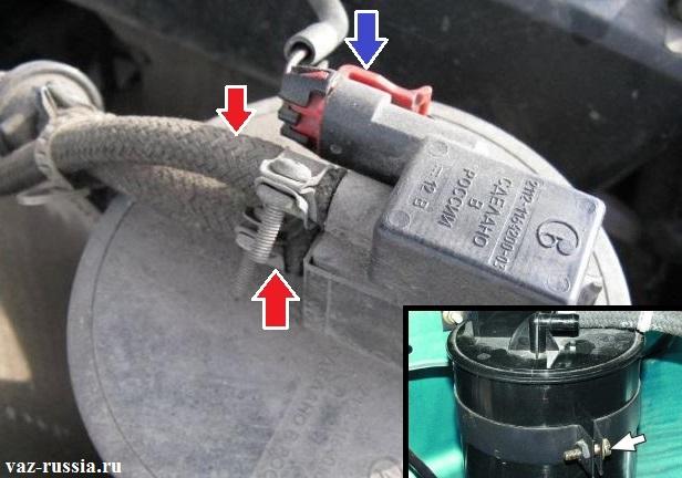 Два шланга подсоединённых к клапану продувки адсорбера, а так же колодка проводов которая подсоединена всё к тому же клапану и болт стягивающих хомут который и удерживает сам адсорбер на одном месте