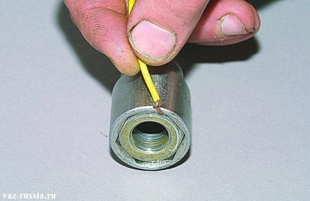Вставление жилок от провода для того чтобы гайка крепления руля плотно закрепилась в головке и не выпадала из неё по мере закручивания
