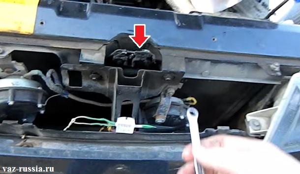 На фотографии стрелкой показано местонахождение замка за который фиксатор капота зацепается при закрывании