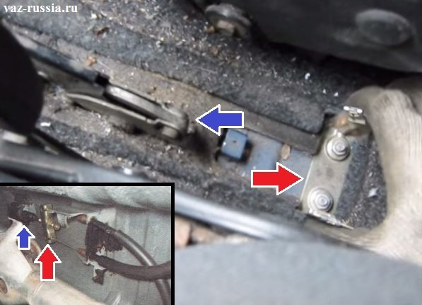 На фотографии показано местонахождение троса ручника в автомобиле