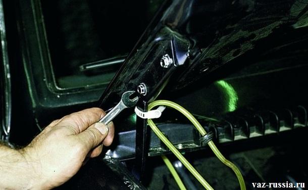 Затягивание ключом всех болтов крепления капота, в то время пока человек удерживает капот