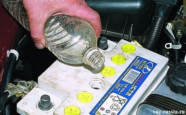 Заливание бутылки с дистиллированной водой в отсек аккумулятора