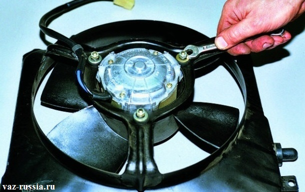 Отворачивание гайки, которая удерживает электродвигатель вентилятора, на кожухе