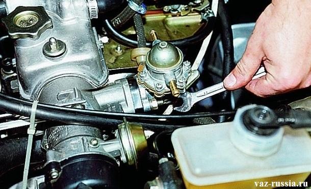 Отворачивание гайки крепления насоса к двигателю