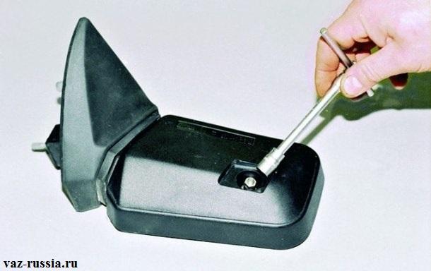 Отворачивание головкой гайки крепления зеркальной части бокового зеркала