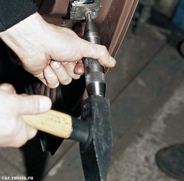 Заворачивание нижнего винта, при помощи молотка и ударной отвертки