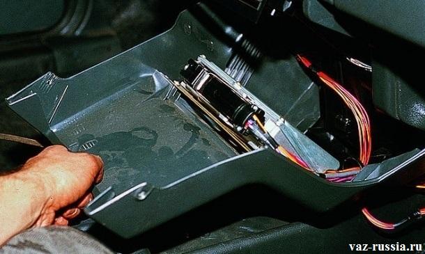 Удерживания нижней накладки консоли приборов после выворачивания двух винтов