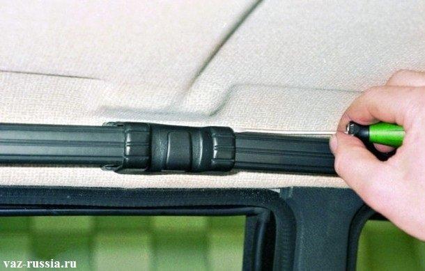 Поддевание центральной заглушки левой ручки, для ее снятия