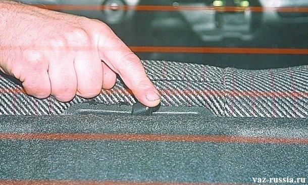 Перемещение центрального рычажка спинки заднего сиденья