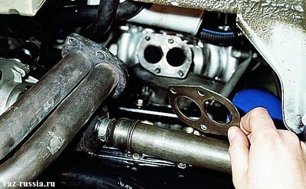 Снятие приемной трубы с автомобиля, а так же снятие с ее при-валочной поверхности, металлической прокладки