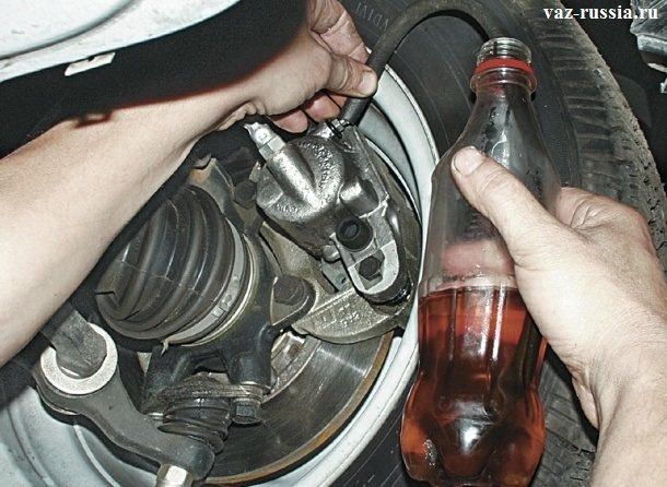 Установка небольшого шланга на прокачной штуцер, и засовывания кончика шланга, в емкость с тормозной жидкостью