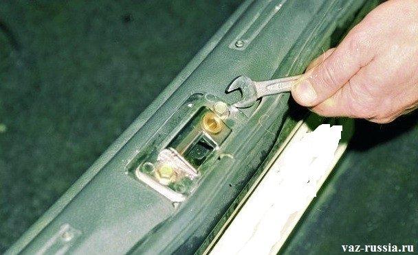 Отворачивание гаечным ключом двух болтов, которые крепят фиксатор