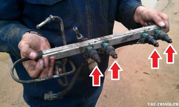Четырьмя красными стрелками указаны форсунки, которые располагаются на топливной рампе и выполняют работу по распылению топлива в цилиндры