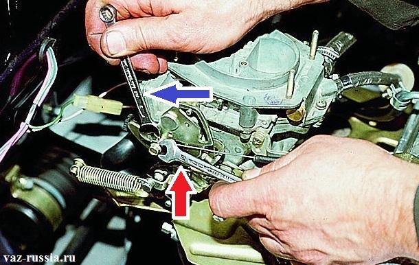 Красной стрелкой указан гаечный ключ при помощи которого требуется отворачивать болт. А синей указан ключ которым нужно удерживать гайку от проворачивания