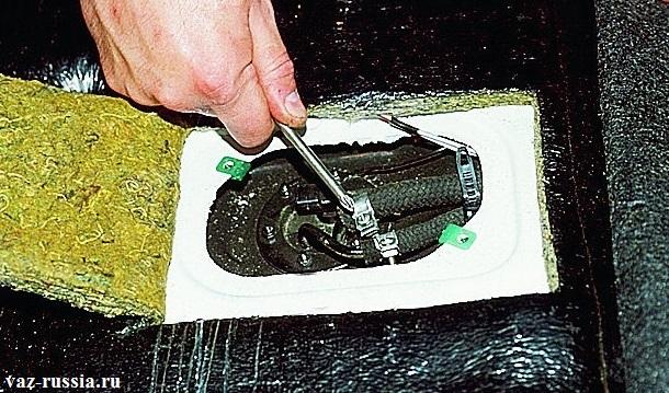 Ослабление отверткой двух винтов, которые крепят шланг подвода и шланг отвода топлива