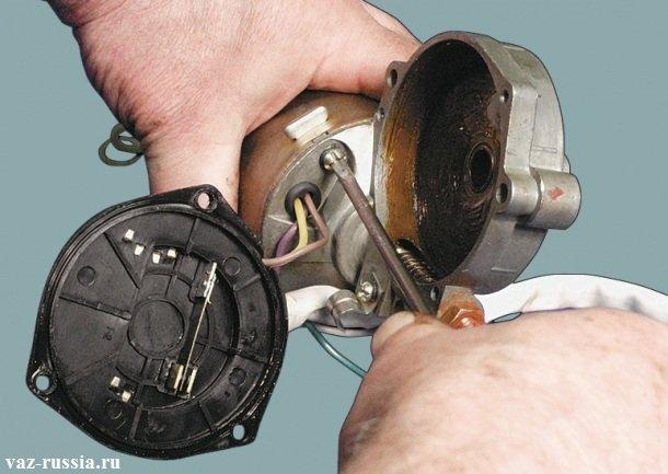 Отворачивание отверткой винтов, которые крепят корпус редуктора