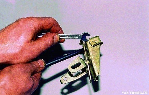 Отворачивание гаечным ключом болта, который крепит фиксатор упругого рычага